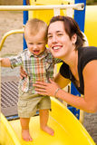 Cute Baby Boy and Mom. A portrait of a cute one year old baby boy at a park with his mom Stock Photo
