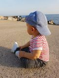 Cute Baby Boy One Year Wearing Striped Clothes. Cute Baby Boy One Year Wearing A Cap Backwards And Striped Clothes, Close Up Portrait. Mediterranean Sea In The royalty free stock photography
