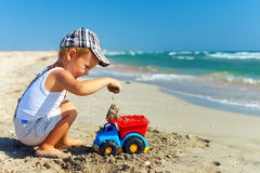 Cute baby boy playing on the beach Stock Image