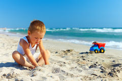 Cute baby boy playing on the beach Stock Photography