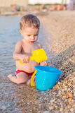 Cute baby boy playing on the beach Stock Images