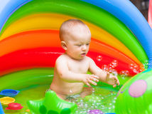 Cute baby boy playing with bubbles in a kiddy pool. Cute baby splashing in a portable baby pool Stock Images