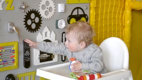 Cute baby boy playing with busy board on the wall. Educational toys stock video footage