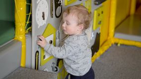 Cute baby boy playing with busy board on the wall. Educational toys. Busy-board for children stock footage