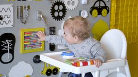 Cute baby boy playing with busy board on the wall. Wooden game board stock video