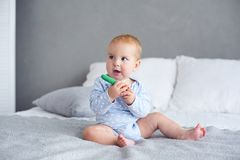 Cute baby boy playing with knitted toy on bed at home.  stock photo