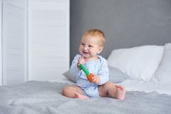 Cute baby boy playing with knitted toy on bed at home.  stock images