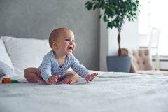 Cute baby boy playing with knitted toy on bed at home.  royalty free stock image