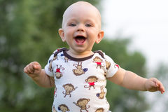 Cute baby boy playing and laughing in the park. Summer is around a lot of greenery  interesting things for crumbs. Kid 1 Royalty Free Stock Photo