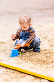 Cute baby boy playing with sand. In a sandbox Stock Photos
