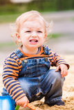 Cute baby boy playing with sand. In a sandbox Royalty Free Stock Image