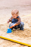 Cute baby boy playing with sand Stock Images