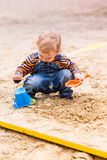 Cute baby boy playing with sand. In a sandbox Stock Photo