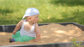 Cute baby boy playing with sand in a sandbox. Summer park and green grass in the background stock video