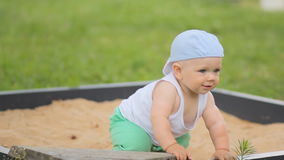 Cute baby boy playing with sand in a sandbox. Summer park and green grass in the background stock footage