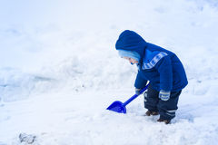 Cute baby boy playing with snow toy shovel. In winter outdoor Stock Images