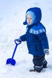 Cute baby boy playing with snow toy shovel. In winter outdoor Royalty Free Stock Image