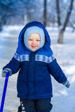 Cute baby boy playing with snow toy shovel Stock Photo