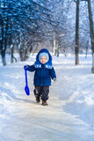 Cute baby boy playing with snow toy shovel Stock Image