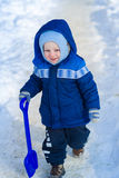 Cute baby boy playing with snow toy shovel Royalty Free Stock Photo