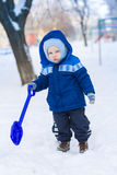 Cute baby boy playing with snow toy shovel. In winter outdoor Stock Photo