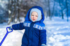 Cute baby boy playing with snow toy shovel Stock Photos