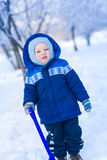 Cute baby boy playing with snow toy shovel Royalty Free Stock Image