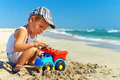 Cute baby boy playing toys on beach Stock Image