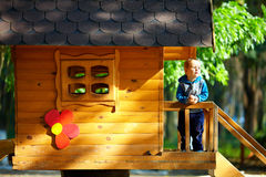 Cute baby boy playing in tree house, outdoor. Cute baby boy playing in tree house, sunny outdoor Stock Images