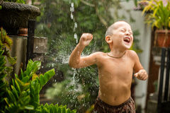 Cute baby boy playing under the rain Royalty Free Stock Image