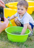 Cute baby boy is playing with water and posing Stock Image