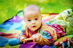 Cute baby boy playing with a wooden rattle toy Royalty Free Stock Images