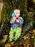 Cute baby boy playing with a wooden rattle toy  and sitting by t Royalty Free Stock Photo