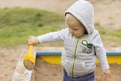Cute baby boy playing wuth sand on the children playground royalty free stock photo