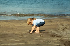 Cute baby boy plays with sand on sandy beach Stock Images