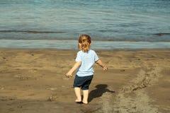 Cute baby boy plays with sand on sandy beach Stock Photos