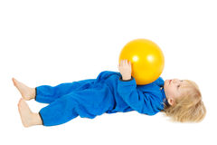 Cute baby boy plays with yellow ball Royalty Free Stock Image