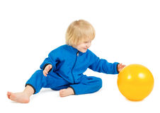 Cute baby boy plays with yellow ball Royalty Free Stock Photography