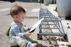 Cute baby boy reading outdoor. Cute little boy reading, sitting on the pavement, in the Parking lot, outdoor Royalty Free Stock Images