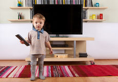 Cute baby boy with remote control in front of the TV. A Cute baby boy with remote control in front of the TV Royalty Free Stock Photos