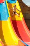 Cute baby boy rides from waterslide Stock Photography