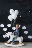 Cute baby boy riding wooden traditional rocking horse toy in room. The boy with balloons. Royalty Free Stock Photography