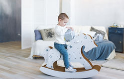 Cute baby boy riding wooden traditional rocking horse toy in white bedroom. Child playing in nursery room. Stock Image