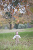 Cute baby boy running through Autumn leaves Stock Photo