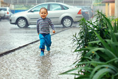Cute baby boy running under the rain Stock Photo