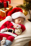Cute baby boy in Santa costume sleeping ext to Christmas gifts Royalty Free Stock Photography