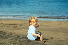 Cute baby boy sits on sand on sandy beach Stock Photography