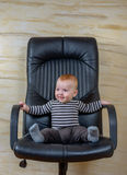 Cute Baby Boy Sitting on Black Office Chair Royalty Free Stock Photos