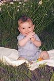 Adorable shy baby boy sitting on blanket Stock Image