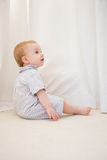Cute baby boy sitting on floor Royalty Free Stock Image